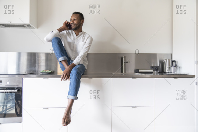Portrait of smiling man on the phone sitting on kitchen counter at home looking at distance