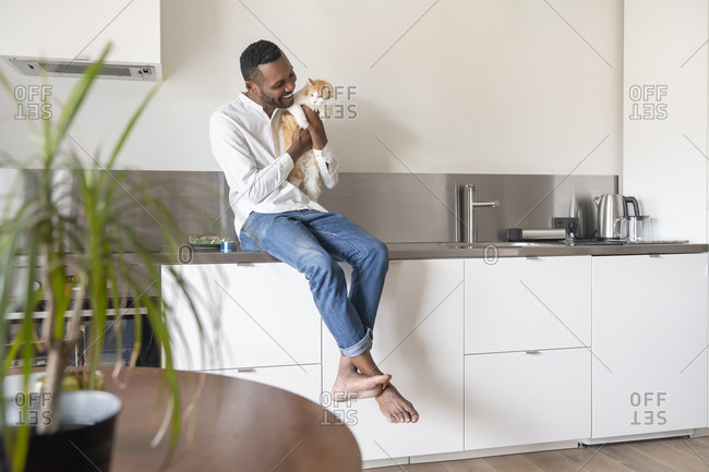 Portrait of smiling man sitting on kitchen counter at home cuddling his cat