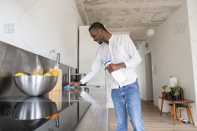 Smiling man standing in kitchen of his apartment cleaning countertop