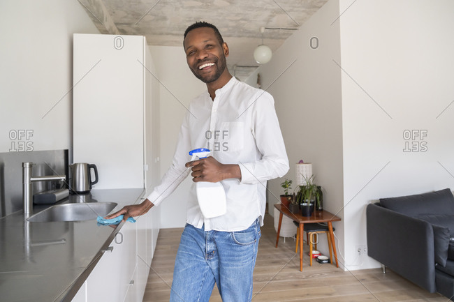 Portrait of laughing man standing in the kitchen cleaning countertop
