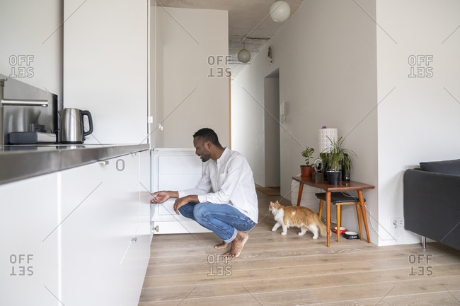 Man crouching in the kitchen looking into freezer