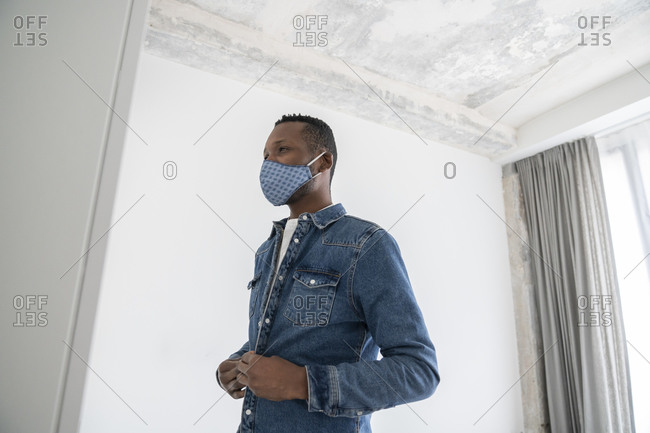 Man wearing reusable face mask indoors putting on his jeans jacket