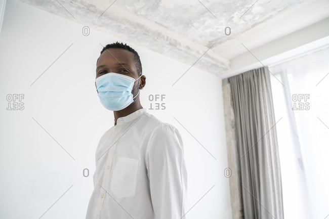 Portrait of man wearing disposable face mask indoors