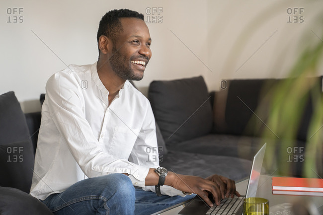 Portrait of laughing man sitting on couch using laptop