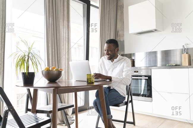 Smiling man sitting at table at home using laptop