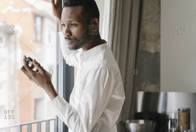 Portrait of pensive businessman with mobile phone looking out of window