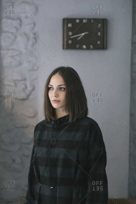 Young woman trying dress looking away while standing in design studio