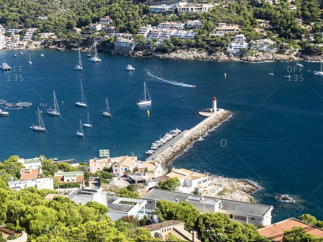 Spain- Mallorca- Andratx- Sailboats sailing in bay of coastal town in summer