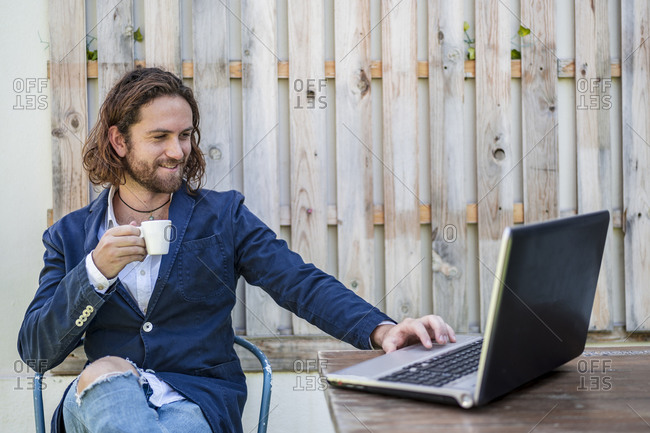 Handsome young businessman drinking espresso while using laptop at cafe