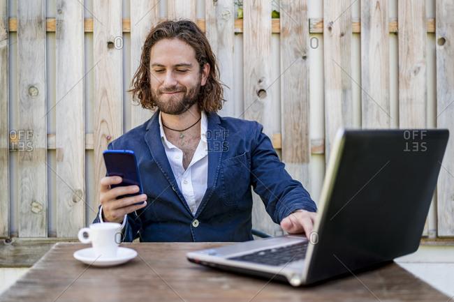 Businessman smirking while using mobile phone sitting at cafe
