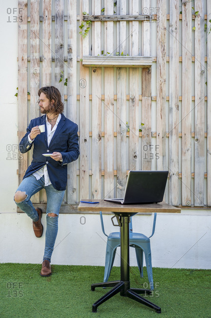 Fashionable young businessman drinking espresso by laptop on table against wooden wall at cafe