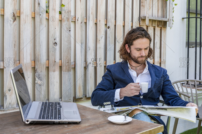 Handsome young businessman with long brown hair reading newspaper while drinking espresso coffee at cafe