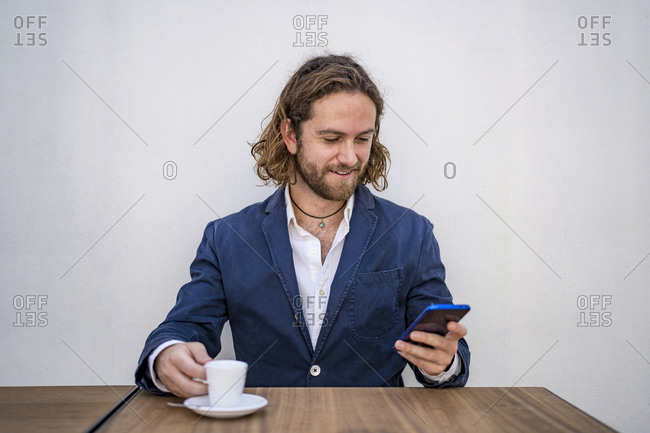 Smiling handsome businessman using smart phone while sitting with espresso at table against white wall in cafe