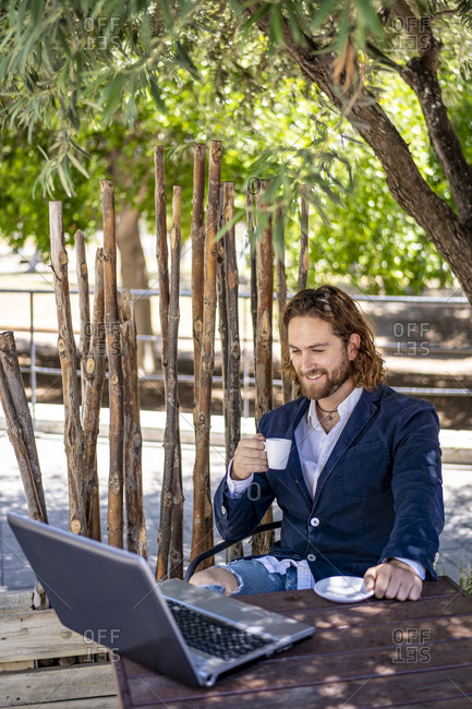 Smiling businessman drinking espresso while sitting with laptop at cafe