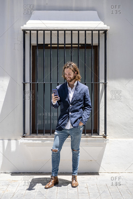 Smiling handsome businessman using smart phone while standing against window