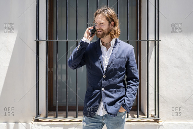 Handsome smiling male professional talking on mobile phone while standing against window