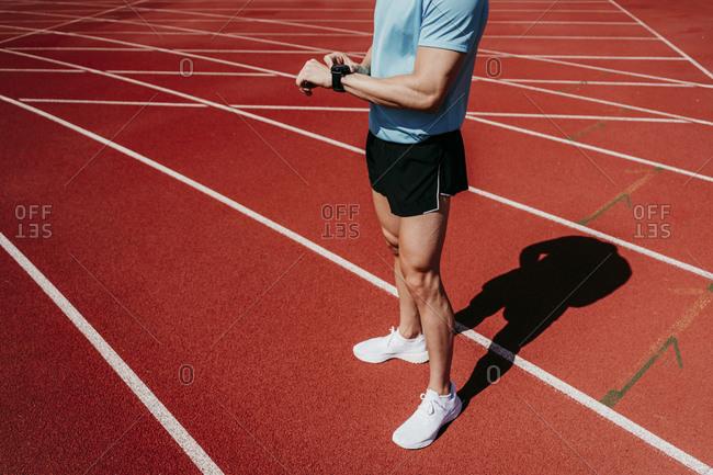 Male athlete on tartan track checking smartwatch