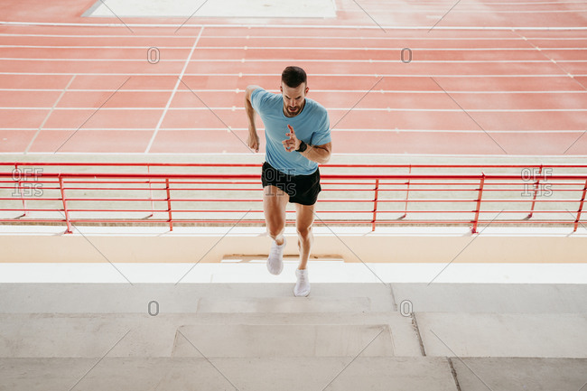 Male athlete running up steps in stadium