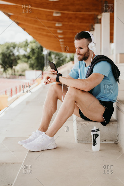 Male athlete with headphones- smartphone and smartwatch having a break sitting on grandstand in stadium