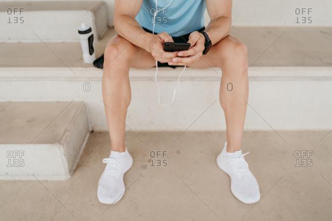 Male athlete having a break sitting on grandstand in stadium using smartphone