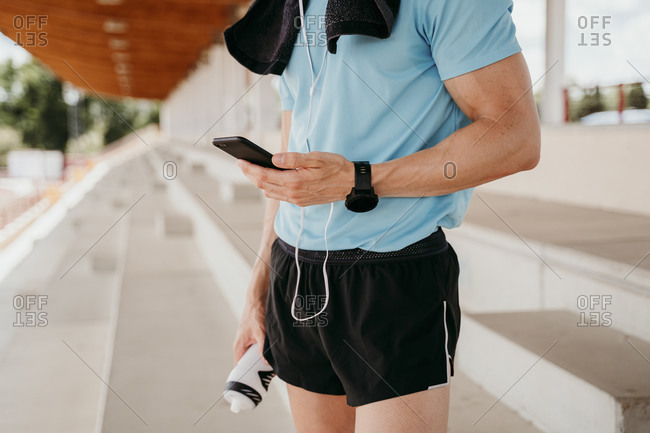 Male athlete checking smartphone on grandstand in stadium