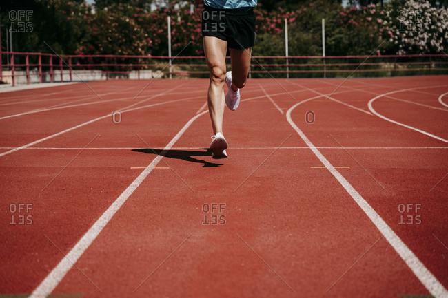Legs of a man running on tartan track