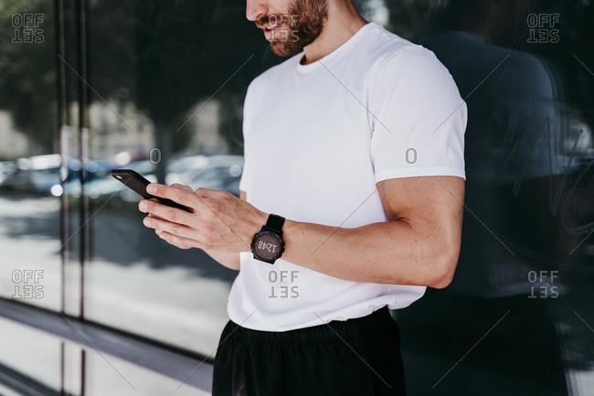 Male athlete having a break checking smartphone
