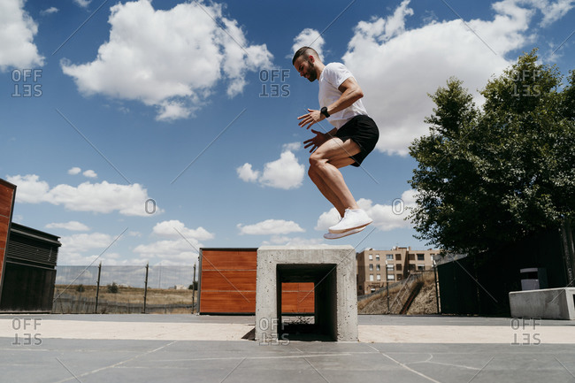 Male athlete jumping over cement block outdoors