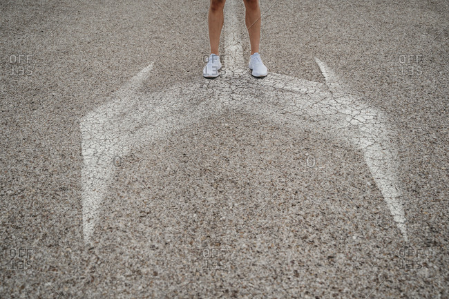 Male athlete standing at arrow signs on the road
