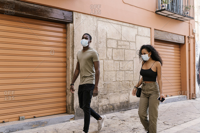 Man and woman wearing masks while walking on city street