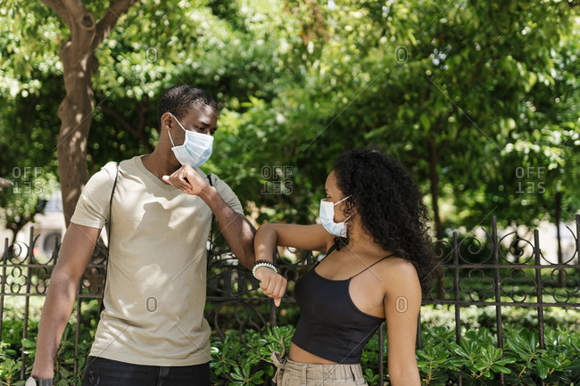 Man and woman wearing masks while greeting each other by touching elbows at park