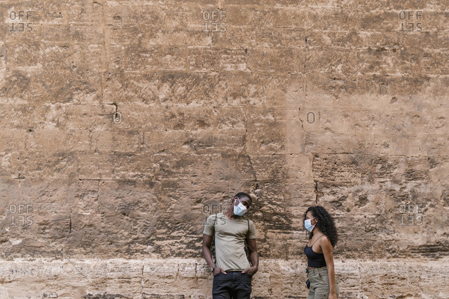 Man and woman wearing masks while talking against weathered wall
