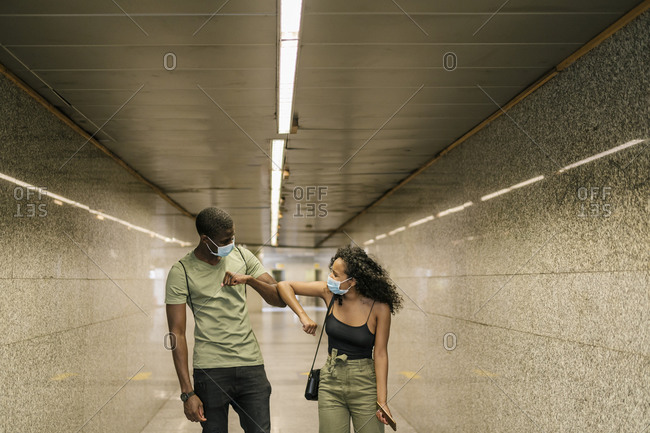 Couple wearing masks while greeting each other with elbows in underground walkway