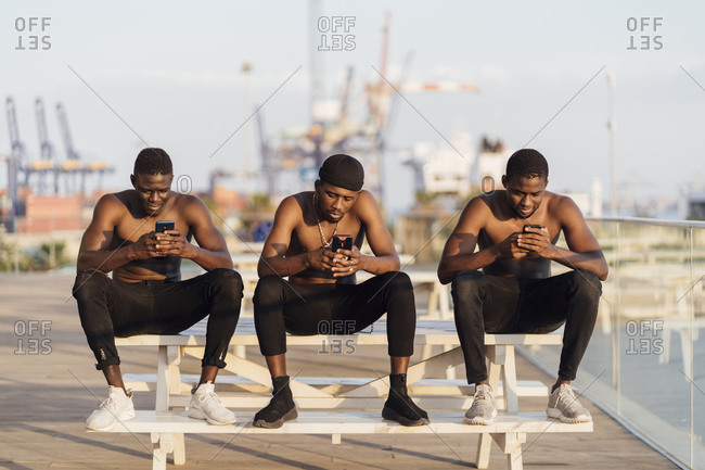 Young shirtless men sitting side by side on picnic table while using smart phones during sunny day