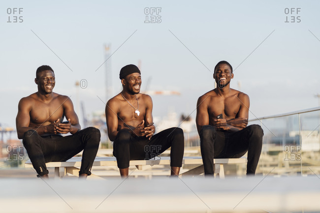 Cheerful young friends sitting shirtless on picnic table against sky