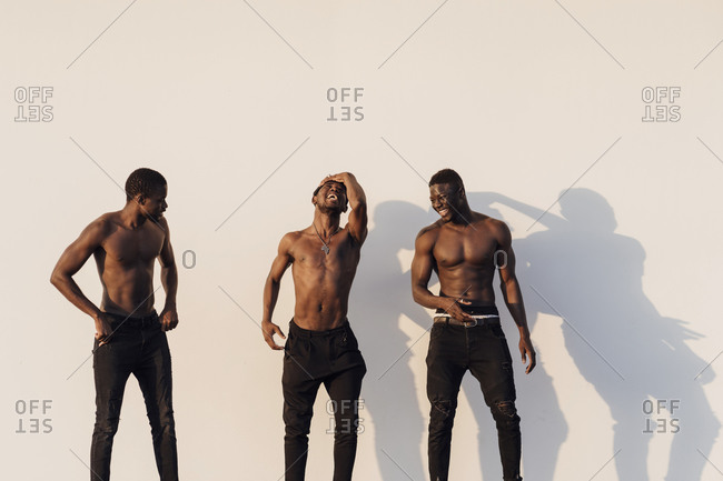Cheerful young male friends standing shirtless against white wall on sunny day