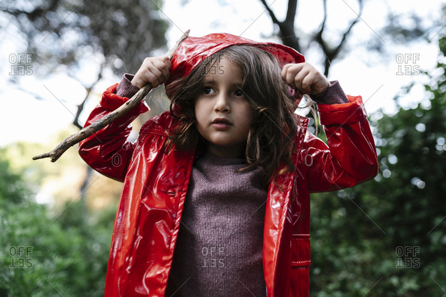 Girl wearing red rain jacket and hood in the woods
