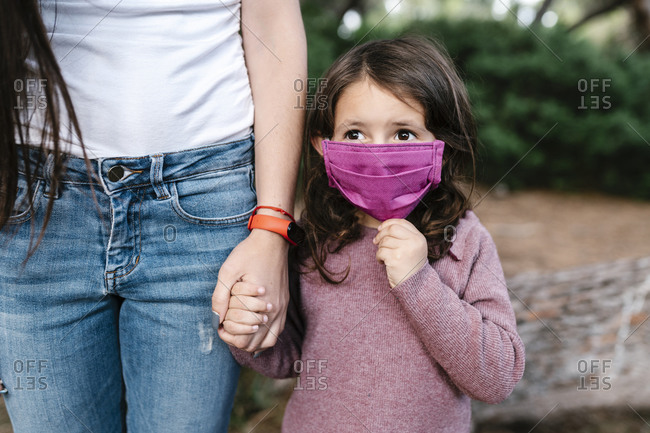 Daughter wearing protective mask and holding hand of her mother