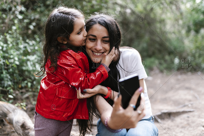 Daughter kissing her mother while taking a selfie in the woods