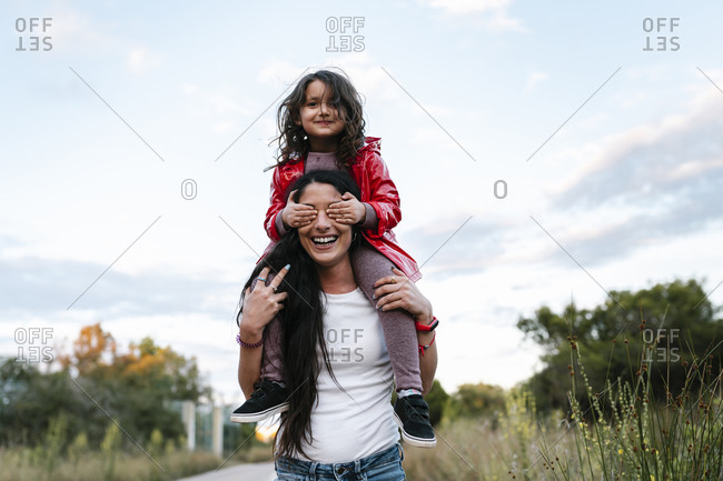 Mother with daughter on her shoulders- girl covering her eyes