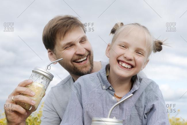 Smiling man and daughter enjoying lemonade against sky