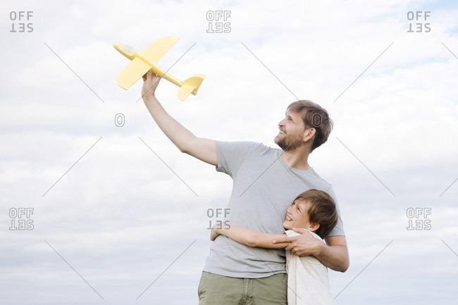 Happy boy embracing father holding toy airplane standing against sky