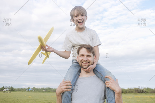 Smiling man with son on shoulders holding toy airplane against sky