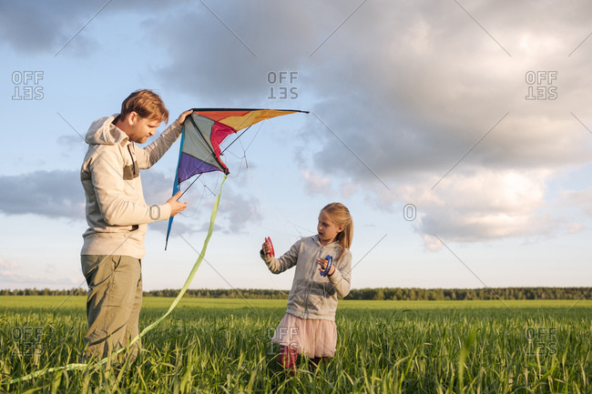 Father and daughter flying kite while standing on green landscape against sky