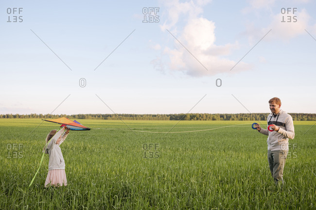 Father holding spools while daughter flying kites on green landscape