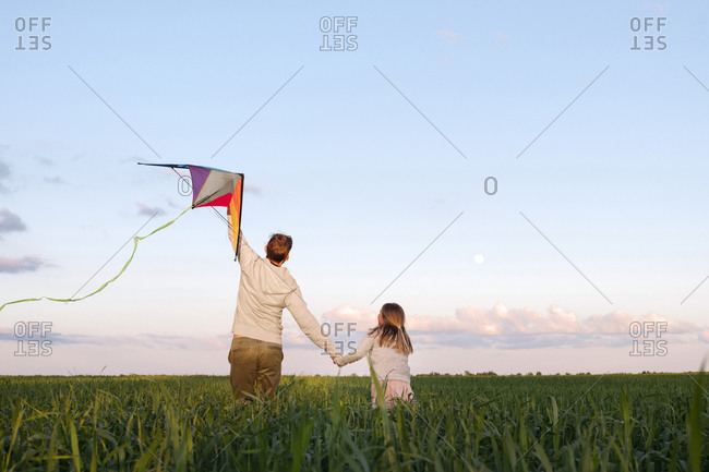 Man holding kite while walking with daughter amidst plants on green landscape