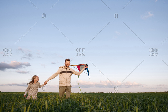 Cheerful father and daughter with kite running on green landscape against sky