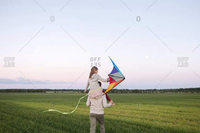 Father carrying daughter on shoulders while walking on grassy landscape at sunset