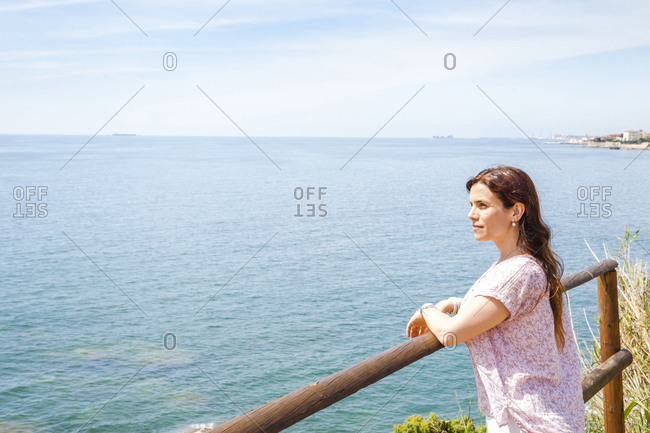 Woman leaning on railing while looking at Ligurian Sea against sky during sunny day