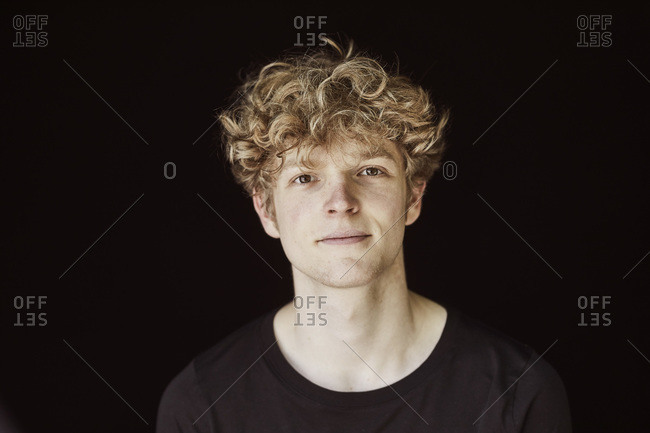 Portrait of young man with curly blond hair against black background